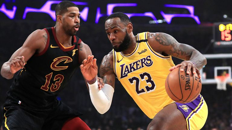 LeBron James drives by former team-mate Tristan Thompson