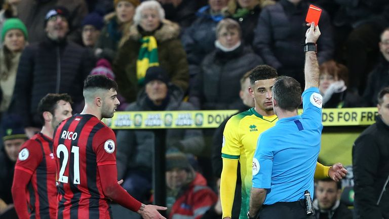 Referee Paul Tierney shows a red card to Norwich's Ben Godfrey after using the VAR monitor to upgrade the booking