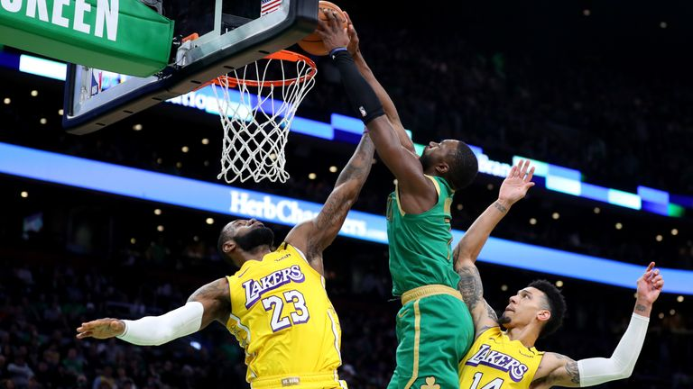 Jaylen Brown of the Boston Celtics dunks over Lebron James