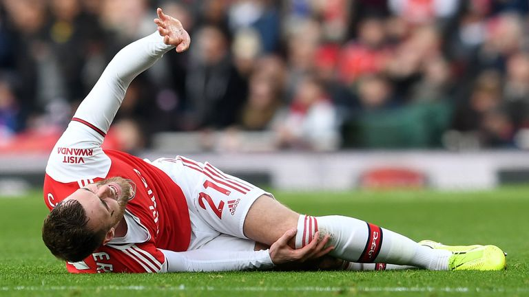 Arsenal's Calum Chambers holds his knee after picking up an injury