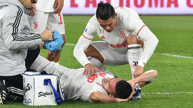 Merih Demiral is comforted by Cristiano Ronaldo as he receives treatment on the pitch