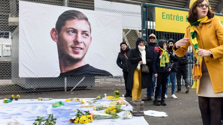 People pay homage and lay flowers in front of a portrait of Nantes' Argentinian forward Emilianio Sala, who died one year ago in a plane crash