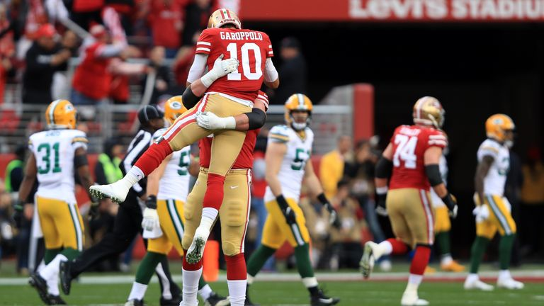 Jimmy Garoppolo of the San Francisco 49ers reacts to a touchdown run by Raheem Mostert in the first quarter against the Green Bay Packers during the NFC Championship game