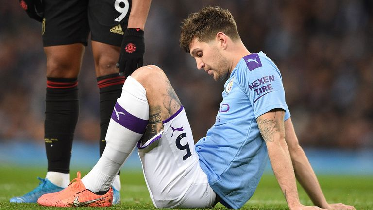 Manchester City's English defender John Stones (R) sits on the pitch injured before being substituted during the English Premier League football match between Manchester City and Manchester United at the Etihad Stadium in Manchester, north west England, on December 7, 2019.
