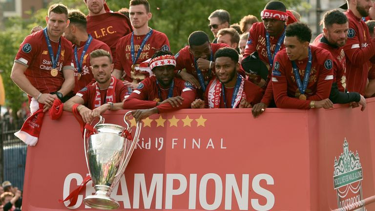 Liverpool players with the Champions League trophy on their open-top bus parade