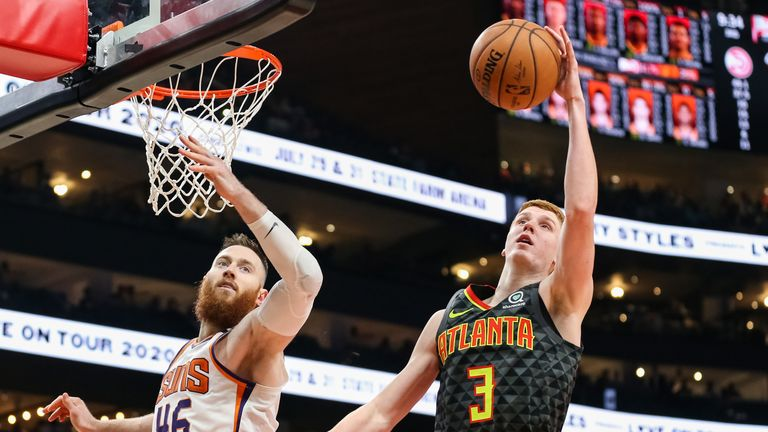 Aron Baynes #46 of the Phoenix Suns and Kevin Huerter #3 of the Atlanta Hawks go up for a loose ball during the second quarter of a game at State Farm Arena on January 14, 2020 in Atlanta, Georgia.