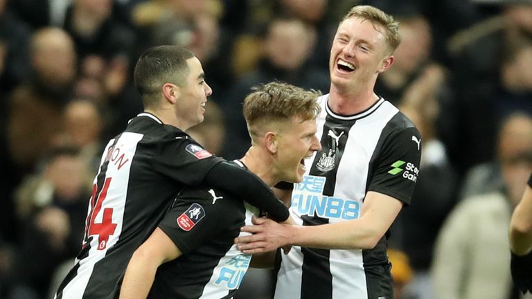 Newcastle United players celebrate after an own goal by Rochdale's Eoghan O'Connell