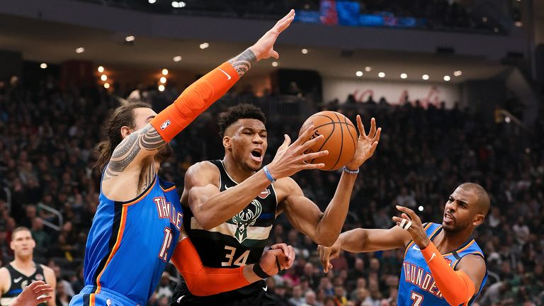 Giannis Antetokounmpo of the Milwaukee Bucks dribbles the ball while being guarded by Steven Adams  and Chris Paul of the Oklahoma City Thunder