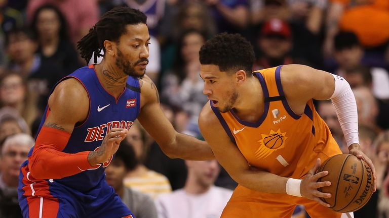 Devin Booker of the Phoenix Suns handles the ball against Derrick Rose of the Detroit Pistons