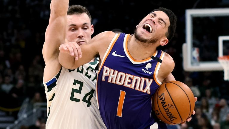 Devin Booker absorbs contact during the Suns' loss to the Bucks