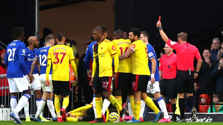 Referee Craig Pawson shows Fabian Delph a red card after fouling Etienne Capoue