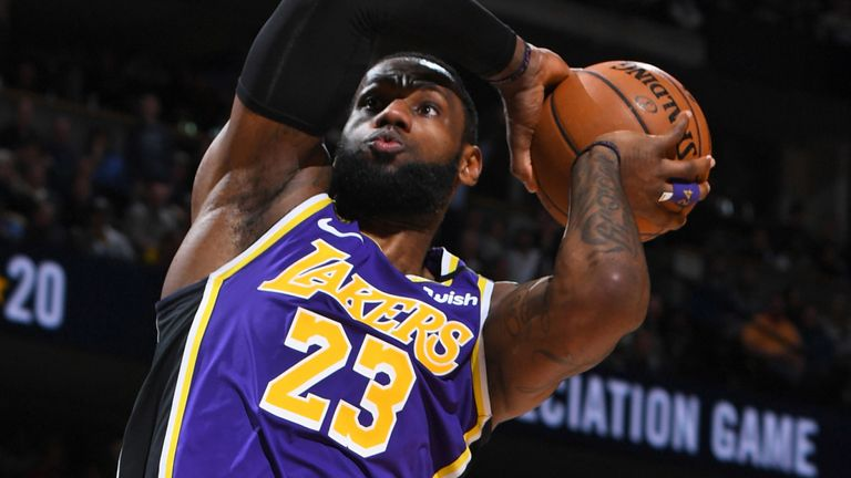 LeBron James soars for a dunk during the Lakers' OT win over the Nuggets