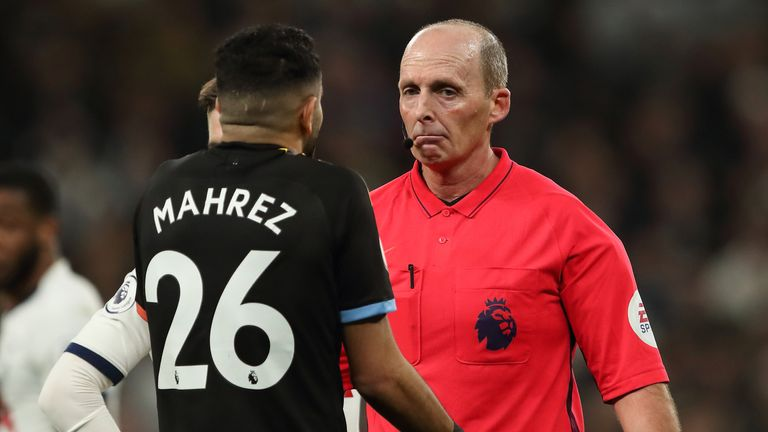 Referee Mike Dean speaks to Riyad Mahrez during Manchester City's game at Tottenham