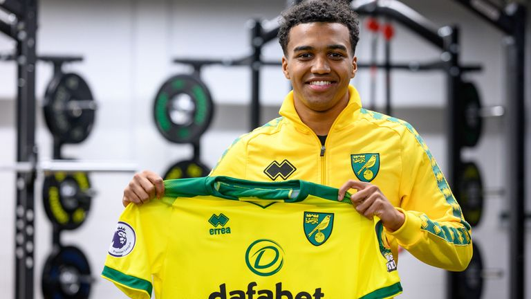 McCallum holds up the Norwich shirt after signing a four-and-a-half-year contract