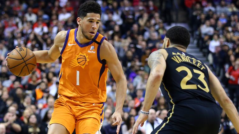 Devin Booker of the Phoenix Suns dribbles the ball as Fred VanVleet of the Toronto Raptors