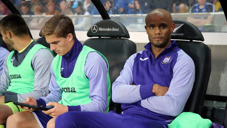 Kompany takes his seat in the dug-out during an Anderlecht game this term