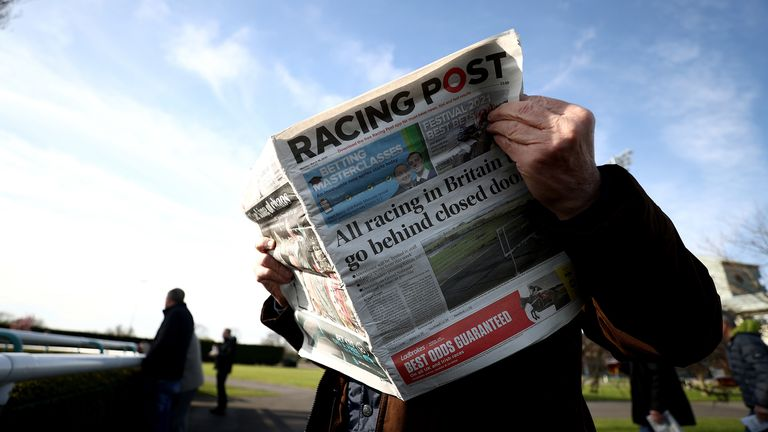 A racegoer reads the Racing Post at Southwell Racecourse.