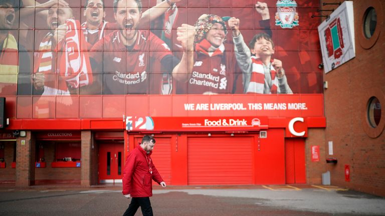 A steward walks outside Liverpool's ground Anfield.