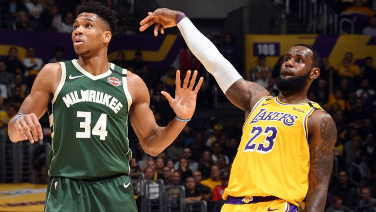 LeBron James of the Los Angeles Lakers holds the follow through while Giannis Antetokounmpo of the Milwaukee Bucks plays defense