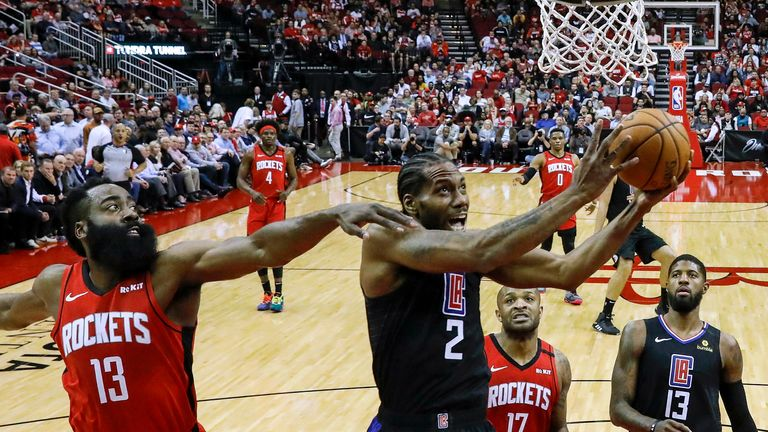 Kawhi Leonard of the LA Clippers drives to the basket while defended by James Harden of the Houston Rockets