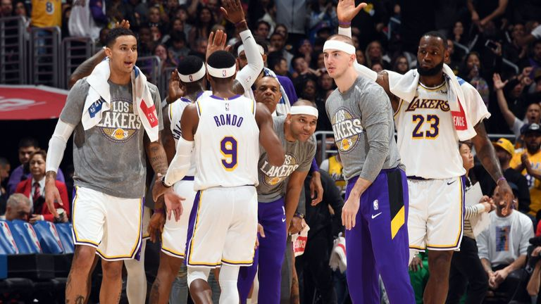 The Los Angeles Lakers players high-five on the sidelines