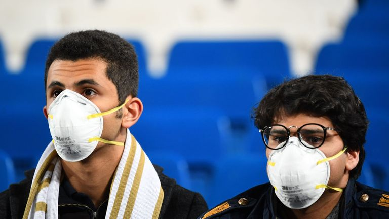 Two fans are pictured wearing masks during El Clasico