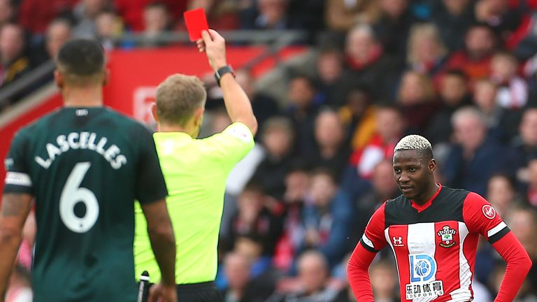 Referee Graham Scott shows Moussa Djenepo a red card following a VAR review for a challenge on Isaac Hayden