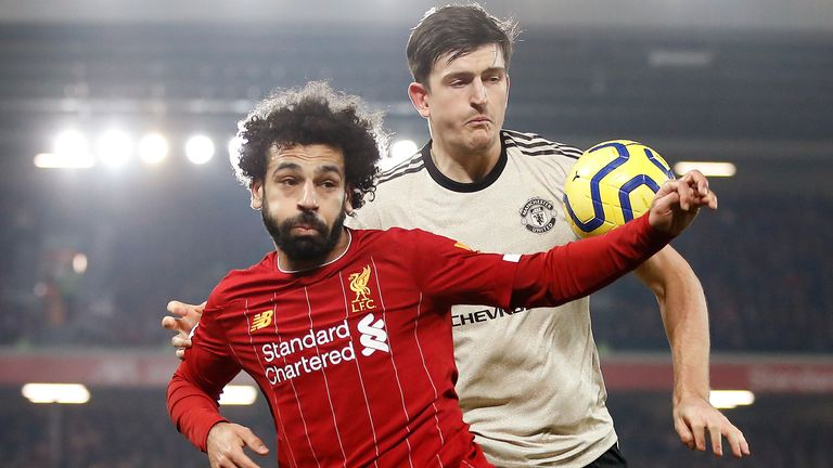 """Liverpool's Mohamed Salah (left) and Manchester United's Harry Maguire battle for the ball during the Premier League match at Anfield, Liverpool. PA Photo. Picture date: Sunday January 19, 2020. See PA story SOCCER Liverpool. Photo credit should read: Martin Rickett/PA Wire. RESTRICTIONS: EDITORIAL USE ONLY No use with unauthorised audio, video, data, fixture lists, club/league logos or """"live"""" services. Online in-match use limited to 120 images, no video emulation. No use in betting, games or single club/league/player publications."""