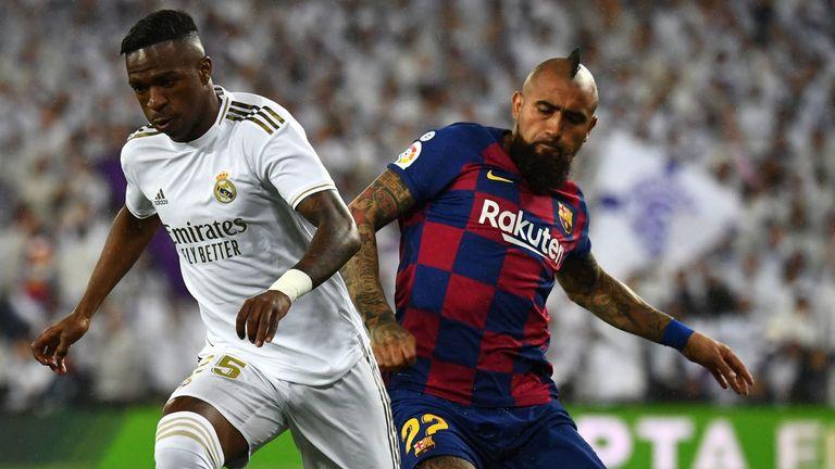 Barcelona midfielder Arturo Vidal challenges Real Madrid's Vinicius Junior