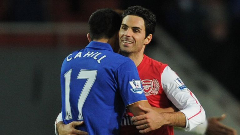 Cahill embraces Arteta during a match in 2011 between Everton and Arsenal