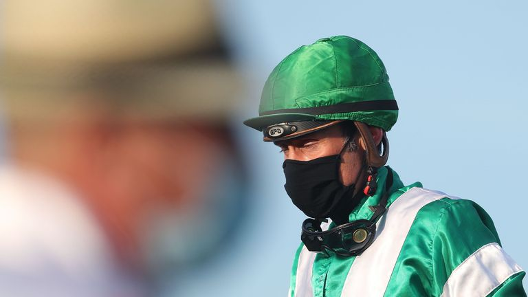 A jockey and a trainer wear protective face masks at the Neue Bult trotting course in Hanover, northwestern Germany, on May 7, 2020, during the first trotting race meeting in Germany following lockdowns amid the novel coronavirus COVID-19 pandemic. (Photo by Ronny Hartmann / AFP) (Photo by RONNY HARTMANN/AFP via Getty Images)
