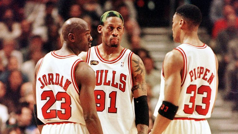 Dennis Rodman of the Chicago Bulls talks to teammates Michael Jordan and Scottie Pippen
