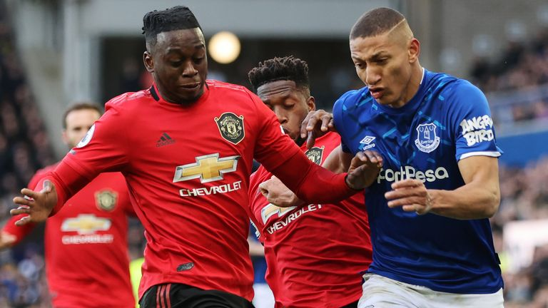 Richarlison of Everton is challenged by Fred and Aaron Wan Bissaka of Manchester United during the Premier League match between Everton FC and Manchester United at Goodison Park on March 01, 2020
