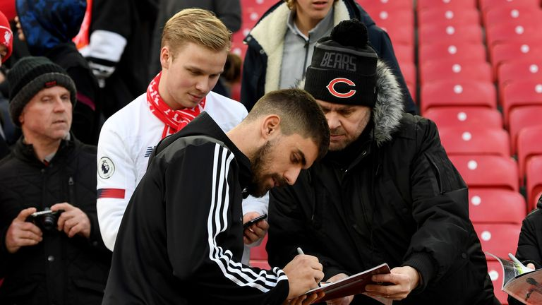 The midfielder signs autographs for supporters at Anfield this season