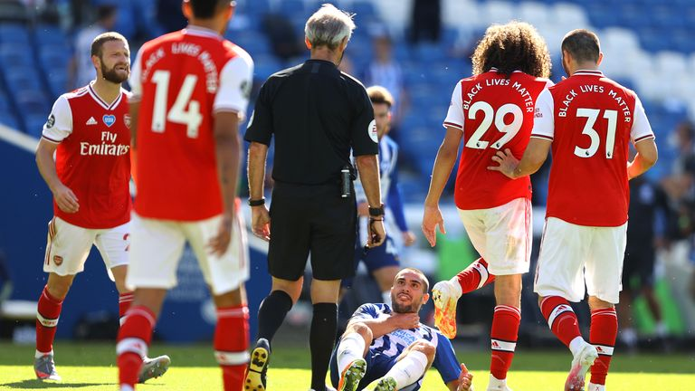 Brighton's Neal Maupay goes down clutching his throat after a clash with Arsenal's Matteo Guendouzi
