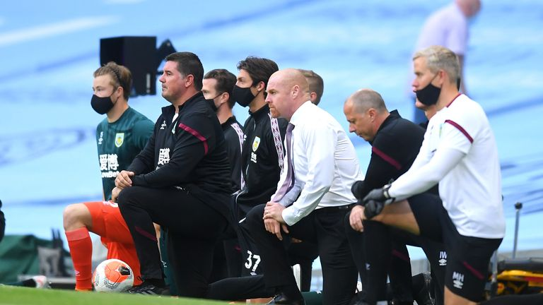 Burnley manager Sean Dyche and his backroom staff take a knee