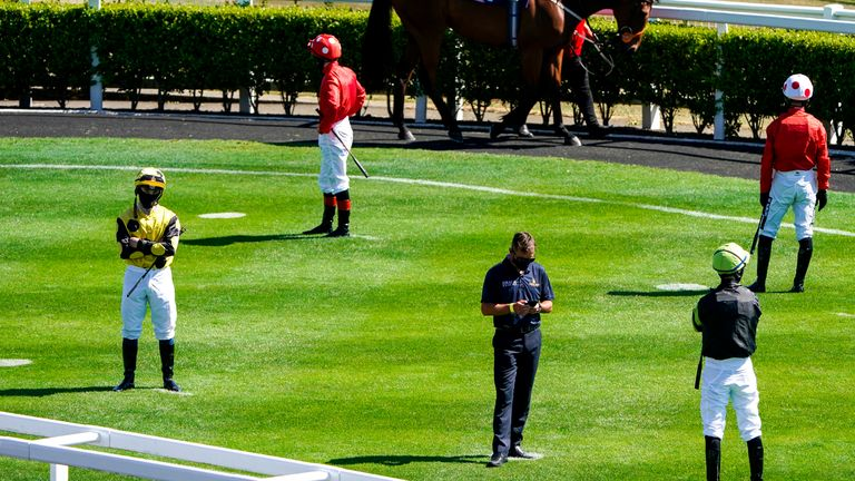 Jockeys maintain social distancing in the parade ring ahead of one of Monday's races at Newcastle