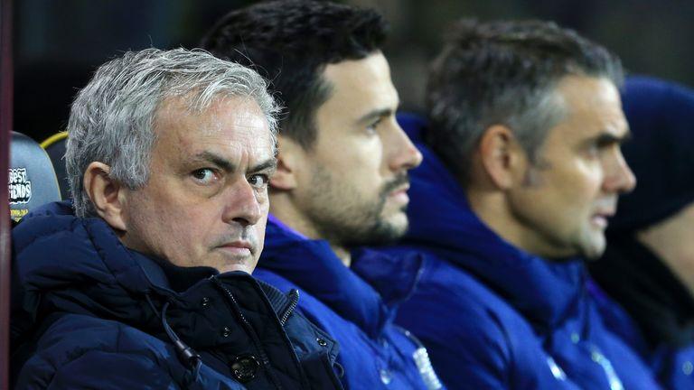 Jose Mourinho looks on alongside his coaching staff before a Premier League match