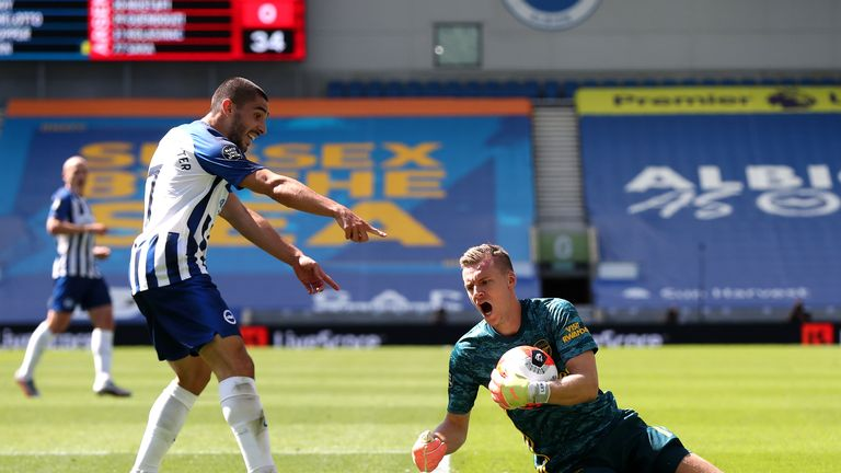Bernd Leno of Arsenal attempts to collect the ball as he collides with Neal Maupay of Brighton and Hove Albion and later goes down injured during the Premier League match between Brighton & Hove Albion and Arsenal FC at American Express Community Stadium on June 20, 2020 in Brighton