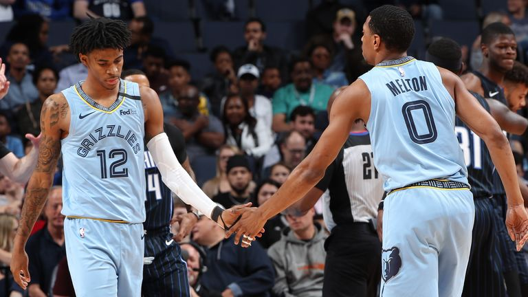 Ja Morant  and De'Anthony Melton of the Memphis Grizzlies hi-five each other during the game against the Orlando Magic