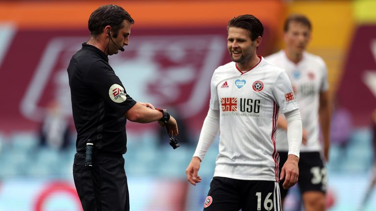 Referee Michael Oliver points to his watch to signal the goal line technology did not give a goal after Sheffield United appeared to score against Aston Villa