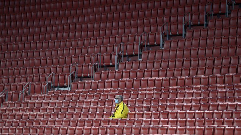 A stadium worker wearing a face mask sits amid empty spectator seats during the Spanish League football match between Sevilla FC and Real Betis at the Ramon Sanchez Pizjuan stadium in Seville on June 11, 2020.