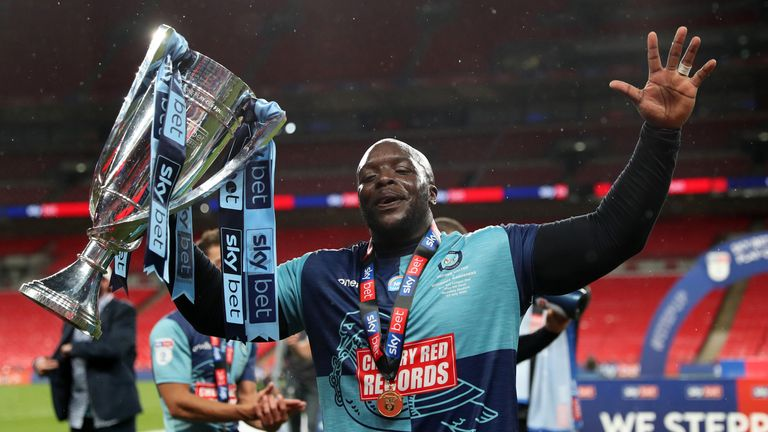 Adebayo Akinfenwa celebrates after Wycombe booked their place in the Championship for next season