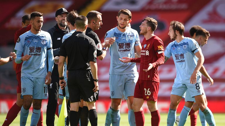 Andy Robertson of Liverpool speaks with Match Referee, David Coote following the Premier League match between Liverpool FC and Burnley FC at Anfield on July 11, 2020 in Liverpool, England. Football Stadiums around Europe remain empty due to the Coronavirus Pandemic as Government social distancing laws prohibit fans inside venues resulting in all fixtures being played behind closed doors