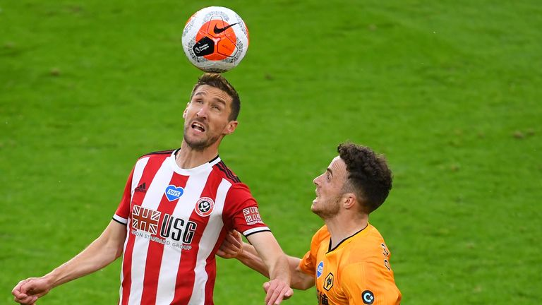 Chris Basham of Sheffield United controls the ball in the air as Diogo Jota of Wolverhampton Wanderers looks on