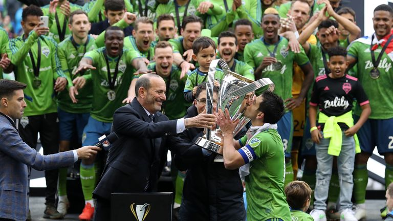MLS Commissioner Don Garber presents the Philip F. Anschutz Trophy to Seattle Sounders FC team captain Nicolas Lodeiro #10 who then kisses it during a game between Toronto FC and Seattle Sounders FC at CenturyLink Field on November 10, 2019 in Seattle, Washington.