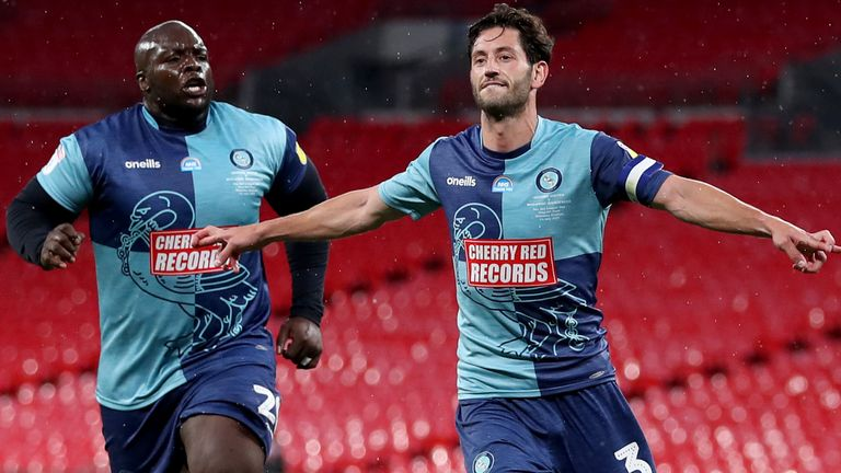 Adebayo Akinfenwa and Joe Jacobson celebrate the latter's penalty against Oxford United