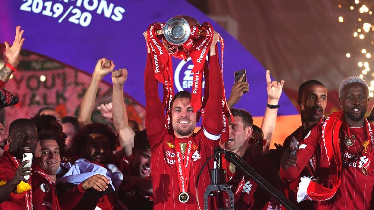 LIVERPOOL, ENGLAND - JULY 22: Jordan Henderson of Liverpool lifts the Premier League trophy following the Premier League match between Liverpool FC and Chelsea FC at Anfield on July 22, 2020 in Liverpool, England.