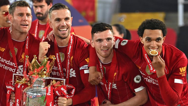 Jordan Henderson celebrates with his Liverpool teammates after lifting the Premier League trophy