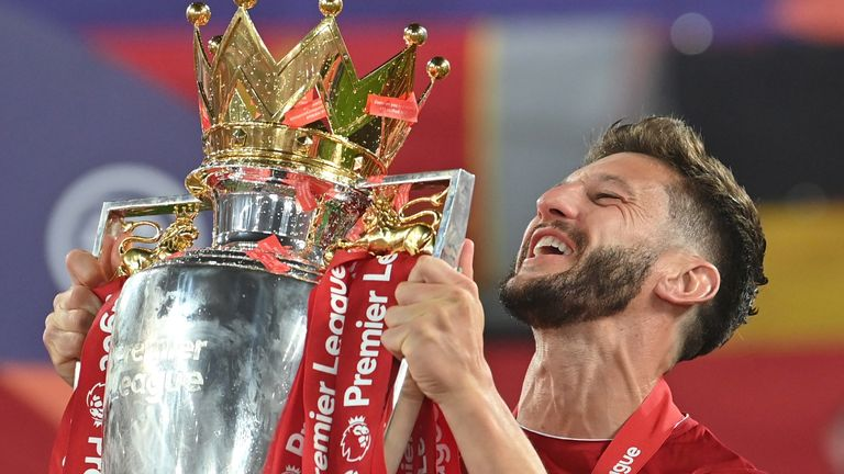 Adam Lallana holding the Premier League trophy aloft after Liverpool's first top-flight title win in 30 years
